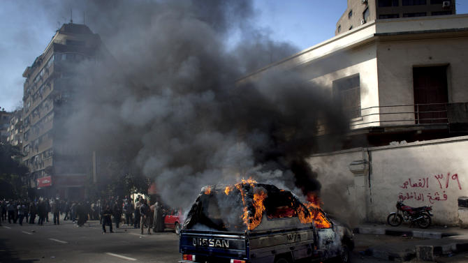 """A police pickup truck burns after being set on fire by Egyptian Ultras, hard-core soccer fans, during an anti government rally in front of the Giza security directorate, background, in Giza, Egypt, Wednesday, March 6, 2013. Hundreds of Ultras rallied to the Giza security directorate chanting anti government slogans, launching fireworks toward the security facility and setting a police pickup truck on fire. Arabic on the wall at right, reads """"March 9th, retribution, hurt the interior ministry."""" (AP Photo/Nasser Nasser)"""