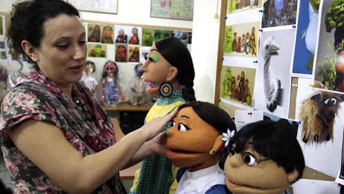 FILE - In a Oct. 13, 2011 file photo, a Pakistani artist, left,  gives final touches to characters of Pakistani Sesame Street in Lahore, Pakistan. The U.S. Embassy in Pakistan says it terminated funding for a $20 million project to develop a local version of Sesame Street amid reports of corruption. Embassy spokesman Robert Raines said Tuesday, June 5, 2012, the U.S. terminated funding but declined to provide details. (AP Photo/K.M.Chaudary, file)