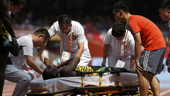 Javon Francis of Jamaica (C) is stretchered away after getting injured in the men's 4 x 400 metres relay heat during the 15th IAAF World Championships at the National Stadium in Beijing