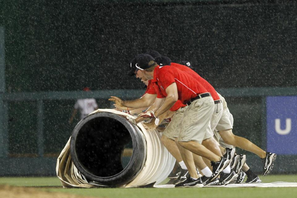 Grounds crew workers roll the tarp out during a rain delay in the seventh inning of a baseball game between the Washington Nationals and San Francisco Giants, Tuesday, July 3, 2012, in Washington. (AP Photo/Alex Brandon)