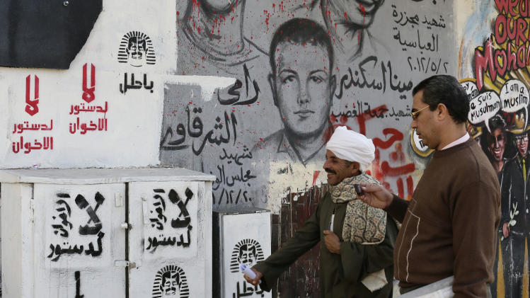 "Egyptian walk next to graffiti and Arabic writing that reads at left, ""no to the Muslim Brotherhood constitution,"" in Tahrir Square in Cairo, Egypt,, Monday, Dec. 10, 2012. The Egyptian military on Monday assumed joint responsibility with the police for security and protecting state institutions until the results of a Dec. 15 constitutional referendum are announced. (AP Photo/Hassan Ammar)"