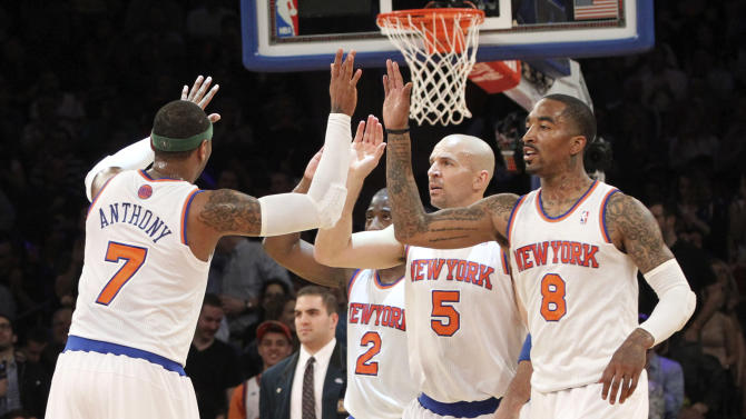 New York Knicks' Carmelo Anthony (7) high fives team mates Raymond Felton (2) Jason Kidd (5) and J.R. Smith (8) during the first half of an NBA basketball game against the Washington Wizards, Tuesday, April 9, 2013, at Madison Square Garden in New York.  (AP Photo/Mary Altaffer)