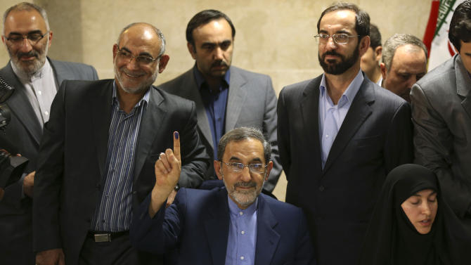 Former Iranian Foreign Minister Ali Akbar Velayati, center, a senior advisor to supreme leader Ayatollah Ali Khamenei, shows his inked finger to media as he registers his candidacy for the upcoming presidential election, at the election headquarters of the interior ministry in Tehran, Iran, Saturday, May 11, 2013. Iranian election authorities say several new high-profile politicians including hardliners, reformists, and allies of outgoing President Mahmoud Ahmadinejad have registered for the June 14 presidential elections. The campaign is taking shape as open season on Ahmadinejad's legacy and his combative style that bolstered his stature among supporters but alarmed critics. Ahmadinejad is barred by law from seeking a third term due to term limits under Iran's constitution. (AP Photo/Ebrahim Noroozi)