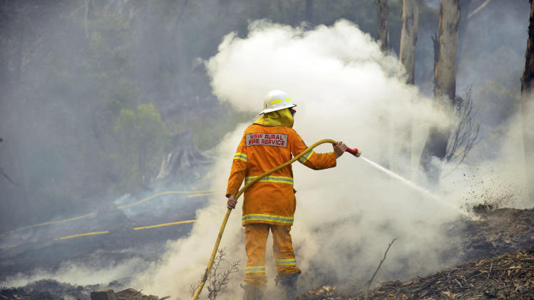 A New South Wales Rural Fire Service volunteer puts out a spot fire in the town of Bell, Australia, on Sunday, Oct. 20, 2013. Firefighters battling some of the most destructive wildfires to ever strike Australia's most populous state were focusing on a major blaze Sunday. Authorities warned that high temperatures and winds were likely to maintain heightened fire danger for days. (AP Photo/AAP Image/Paul Miller) NO ARCHIVING, AUSTRALIA OUT, NEW ZEALAND OUT, PAPUA NEW GUINEA OUT, SOUTH PACIFIC OUT, NO SALES