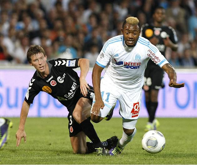 Marseille's Jordan Ayew, right, challenges for the ball with Stade de Reims' defender Franck Signorino during their League One soccer match, at the Velodrome Stadium, in Marseille, southern France, Sa