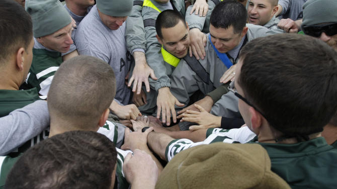U.S. soldiers put their hands together before a football game to mark Thanksgiving at the U.S.-led coalition base in Kabul, Afghanistan, Thursday, Nov. 22, 2012. (AP Photo/Musadeq Sadeq)