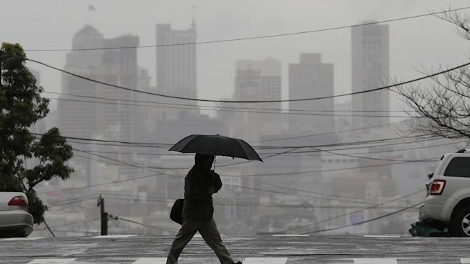 A man carries an umbrella as he crosses Vermont Street with the San Francisco skyline in the background in San Francisco, Tuesday, Feb. 19, 2013. (AP Photo/Jeff Chiu)