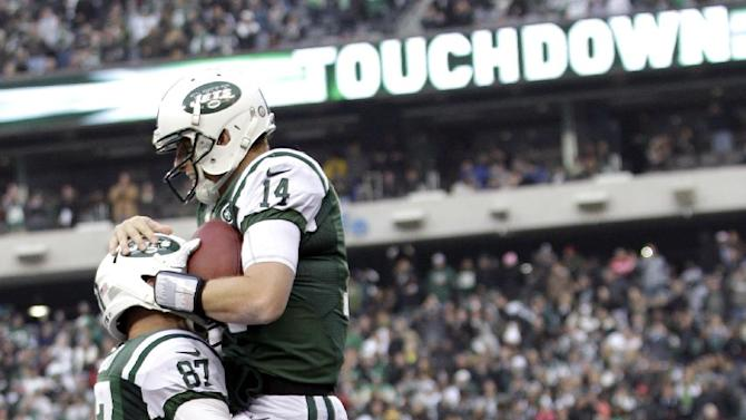 New York Jets quarterback Greg McElroy (14) is lifted by teammate Konrad Reuland after throwing a 1-yard touchdown pass to tight end Jeff Cumberland during the second half of an NFL football game against the Arizona Cardinals, Sunday, Dec. 2, 2012, in East Rutherford, N.J. (AP Photo/Kathy Willens)