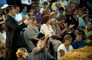 Ryan Rhodes of the Iowa Tea Party Revolution heckles from the crowd as US President Barack Obama speaks at a town hall style meeting in Decorah, Iowa, August 15, 2011, during his three-day bus tour in the Midwest centering on ways to grow the economy