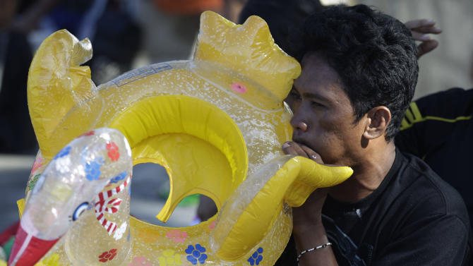 A Filipino man inflates a float while his family swims at the polluted waters of Manila's bay, Philippines as they celebrate Easter Sunday, March 31 2013. Despite a city-imposed swimming ban, many poor Filipinos set up makeshift tents and swam along the bay to cool themselves from summer's sweltering heat. (AP Photo/Aaron Favila)