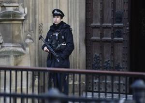 An armed police officer guards outside of the Houses …