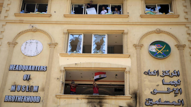 A protester waves an Egyptian national flag as others ransack the Muslim Brotherhood headquarters in the Muqatam district in Cairo, Monday, July 1, 2013. Protesters stormed and ransacked the headquarters of President Mohammed Morsi's Muslim Brotherhood group early Monday, in an attack that could spark more violence as demonstrators gear up for a second day of mass rallies aimed at forcing the Islamist leader from power. (AP Photo/Khalil Hamra)