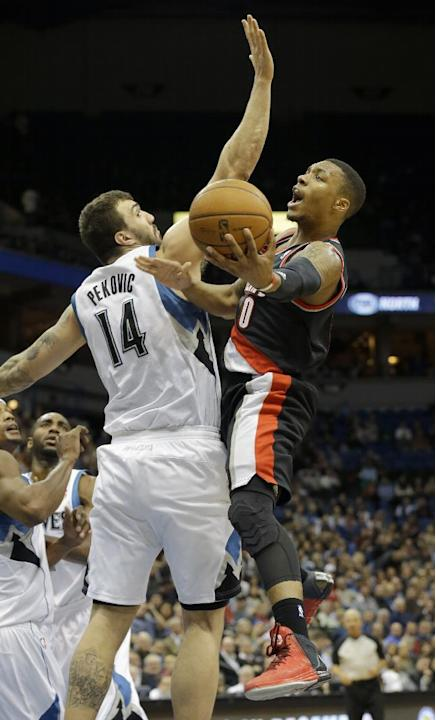 Portland Trail Blazers guard Damian Lillard, right, goes up against Minnesota Timberwolves center Nikola Pekovic (14), of Montenegro, for a shot during the second quarter of an NBA basketball game in
