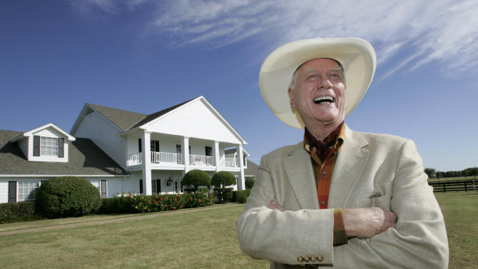 "FILE - In this Oct. 9, 2008, file photo, the late Actor Larry Hagman poses in front of the  Southfork Ranch mansion made famous in the television show, ""Dallas"",  in Parker, Texas. Tourists have been flocking to Southfork Ranch since the early years of the classic series, which ran from 1978 to 1991. And a new ""Dallas"" starting its second season on TNT on Monday and the recent death of the show's star, Larry Hagman, who legendarily played conniving Texas oilman J.R. Ewing, have also spurred fans to visit. (AP Photo/Tony Gutierrez, file)"