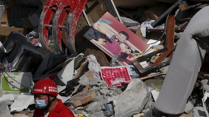 A photo of a child is seen among the ruins of a 17-storey apartment building that collapsed after an earthquake hit Tainan