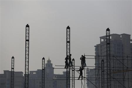 Workers install scaffolding at a construction site in front of residential buildings during a hazy day in Shanghai