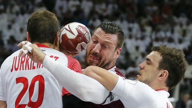 Vidal of Qatar is blocked by Jurkiewicz and Jurecki of Poland during their semi-final match of the 24th Men's Handball World Championship in Doha
