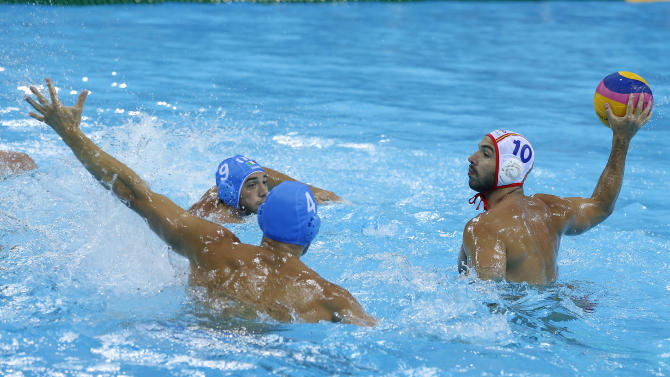Felipe Perrone Rocha, right,  of Spain takes a shot at goal as Pietro Figlioli, center, and Christian Presciutti of Italy defend during their men's water polo preliminary round match at the 2012 Summer Olympics, Monday, Aug. 6, 2012, in London. (AP Photo/Alastair Grant)