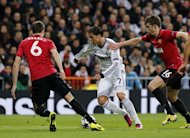 Real Madrid's Portuguese forward Cristiano Ronaldo (C) vies with Manchester United's English midfielder Michael Carrick (R) during the UEFA Champions League round of 16 first leg football match Real Madrid CF vs Manchester United FC at the Santiago Bernabeu stadium in Madrid on February 13, 2013. The match ended in a 1-1 draw