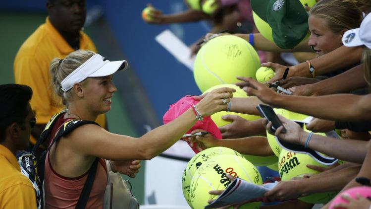 Caroline Wozniacki of Denmark signs autographs after defeating Andrea Petkovic of Germany during their match at the 2014 U.S. Open tennis tournament in New York