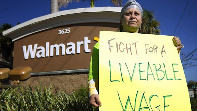 Nawal Elmilliax joins the protest against Wal-Mart in Boynton Beach, Fla., Friday, Nov 23, 2012. Wal-Mart employees and union supporters are taking part in today's nationwide demonstration for better pay and benefits A union-backed group called OUR Walmart, which includes former and current workers, was staging the demonstrations and walkouts at hundreds of stores on Black Friday, the day when retailers traditionally turn a profit for the year. (AP Photo/J Pat Carter)