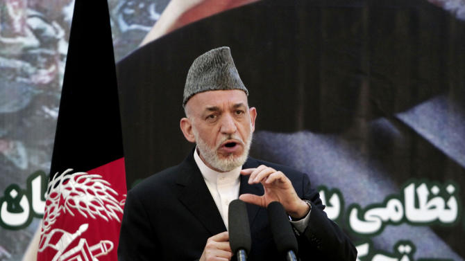 FILE - In this Tuesday, June 18, 2013, file photo, Afghan President Hamid Karzai speaks at a press conference during a ceremony at a military academy on the outskirts of Kabul, Afghanistan. Karzai's office said he signed a decree on Saturday, July 20, 2013, approving a new law governing next year's presidential and provincial elections, an important step toward a smooth transition of power in 2014. (AP Photo/Rahmat Gul, File)