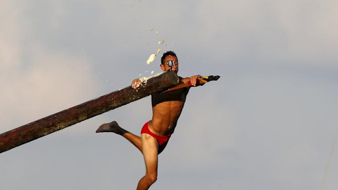 "A competitor grabs the final flag as he falls off the ""gostra"", a pole covered in grease, during the celebrations for the religious feast of St Julian, patron of the town of St Julian's"