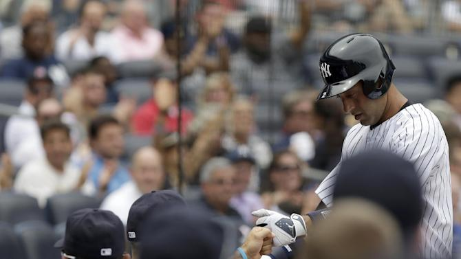 New York Yankees' Derek Jeter is greeted by teammates after scoring a run during the first inning of a baseball game against the Kansas City Royals at Yankee Stadium, Thursday, July 11, 2013 in New York. (AP Photo/Seth Wenig)