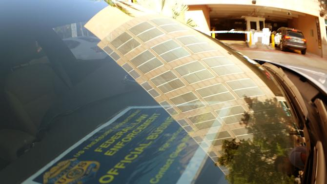 A building housing offices of CONCACAF, the soccer federation that governs North America, Central America and the Caribbean, is reflected on the windshield of an FBI vehicle in Miami Beach