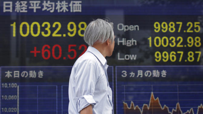 A man strolls past an electronic stock sign board outside a securities firm in Tokyo, Japan, Wednesday, July 6, 2011. Asian stock markets swung back and forth Wednesday as investors proceeded cautiously following a weak performance on Wall Street and a downgrade of Portugal's debt rating. Japan's Nikkei 225 index rose 0.5 percent to 10,018.55, above the psychologically important 10,000 mark for the second time this week. (AP Photo/Itsuo Inouye)