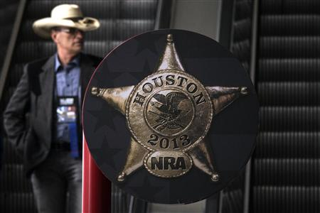 A man rides down an escalator at the George R. Brown Convention Center, ahead of the National Rifle Association's (NRA) annual meeting in Houston, Texas May 2, 2013. REUTERS/Adrees Latif