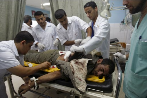 Palestinian medics treat a man wounded by Israeli fire in a hospital in Dir al-Balah