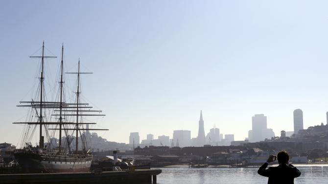 Man takes a photograph of the city skyline from Aquatic Park in San Francisco, California