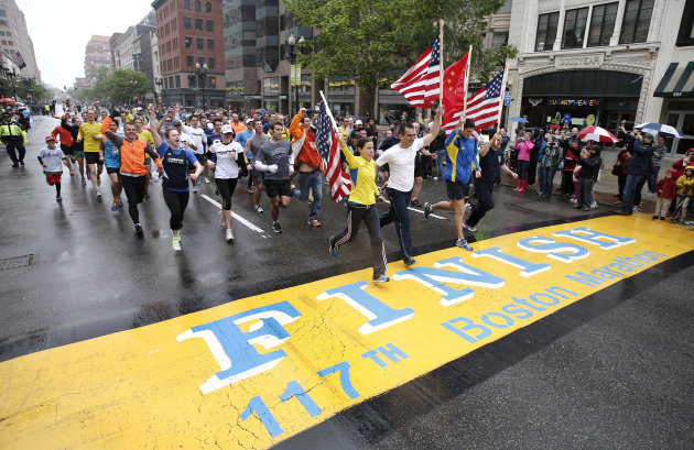 Runners who were unable to finish the Boston Marathon on April 15 because of the bombings cross the finish line on Boylston Street after the city allowed them to finish the last mile of the race in Bo