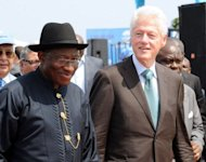 Nigerian President Goodluck Jonathan (L) and former US president Bill Clinton arrive on February 21, 2013, to attend the inauguration ceremony for a giant housing project being built on an artificial terrain and expected to house 250,000 people.