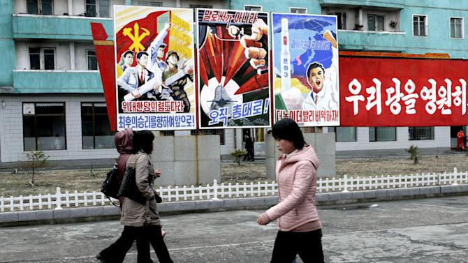 """North Koreans walk past posters reading """"Forward to the ultimate victory under the leadership of the great party!"""" left,  """"not with words but with arms,"""" center, and """"Higher, faster,"""" right, on Tuesday, March 19, 2013, on a street in Phyongchon District in Pyongyang, North Korea.  The banner partially shown at right reads in its entirety """"Let's strengthen and enhance our party as the party of Kim Il Sung and Kim Jong Il!"""" (AP Photo/Jon Chol Jin)"""