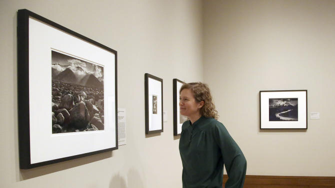 """This March 14, 2014 photo shows Karen Hellman, Assistant Curator Department of Photographs examining a photo exhibit entitled, """"In Focus: Ansel Adams"""" at the J. Paul Getty Museum in Los Angeles. Toward the end of his life, photographer Ansel Adams pored over thousands of negatives he'd carefully kept since his teens and set aside 70 that he considered his best works of art. He offered to sell sets of 25 _ with strings attached: Adams would select 10 and let buyers choose the other 15; the images printed by Adams himself could never be resold, only left to a museum. The few dozen who made the cut included the late Leonard and Marjorie Vernon, whose collection was given to the J. Paul Getty Museum and is the centerpiece of """"In Focus: Ansel Adams."""" (AP Photo/Nick Ut)"""