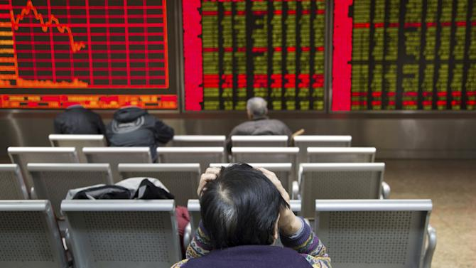 An investor sits in front of an electronic board showing stock information at a brokerage house in Beijing