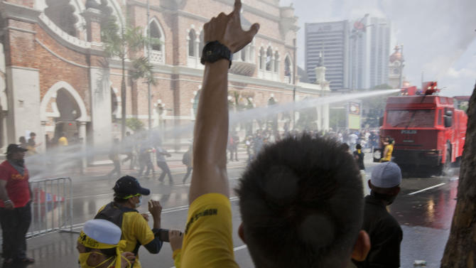Protesters charge at a police vehicle as it sprays them with its water cannons in Kuala Lumpur, Malaysia, Saturday, April 28, 2012. Malaysian police fired tear gas and chemical-laced water Saturday at thousands of demonstrators demanding an overhaul in electoral policies that they call biased ahead of national polls expected soon. At least 25,000 demonstrators had swamped Malaysia's largest city in one of the Southeast Asian nation's biggest street rallies in the past decade. (AP Photo/Mark Baker)