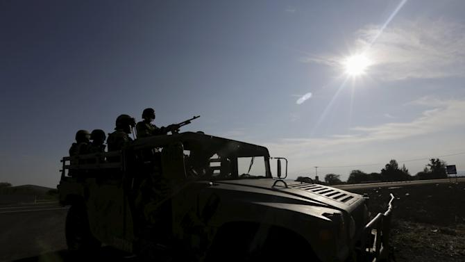 Soldiers atop a vehicle arrive at a ranch where a firefight took place on Friday in Tanhuato