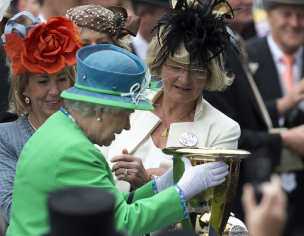 Britain's Queen Elizabeth II hands the trophy for the Diamond Jubilee stakes to Mrs Barry Hawkes, wife of one of the five owners of the Australian horse Dark Caviar who won the race the fifth day of Royal Ascot horse race meeting at Ascot, England, Saturday, June 23, 2012. (AP Photo/Alastair Grant)