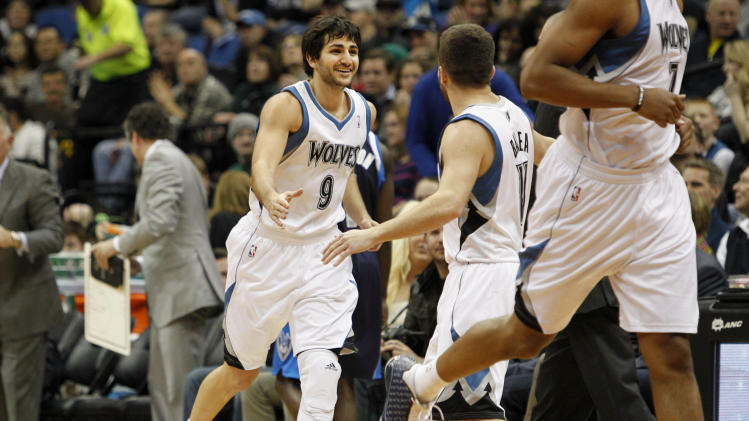 Minnesota Timberwolves point guard Ricky Rubio (9), of Spain, celebrates with teammate Jose Juan Barea (11) during a time out in the first half on an NBA basketball game against the Dallas Mavericks, Saturday, Dec. 15, 2012, in Minneapolis. Rubio was making his season debut after recovering from surgery on his left knee. (AP Photo/Genevieve Ross)