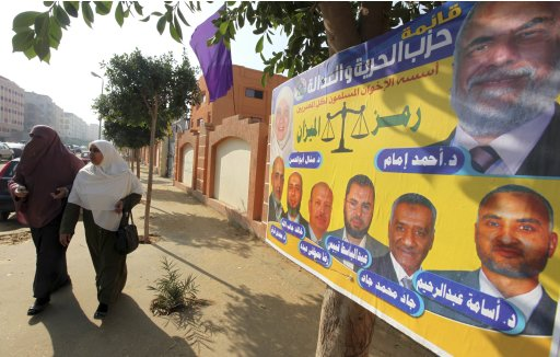 Women walk beside an election poster by Egypt's Muslim Brotherhood
