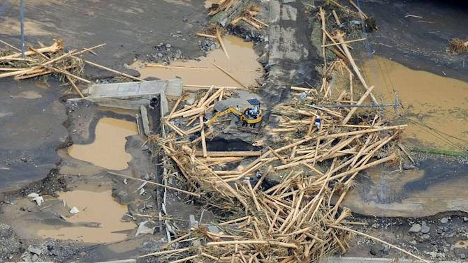 Riverbanks are covered with mud and woods carried by floodwater in Takeda, Kumamoto Prefecture, Japan, Thursday, July 12, 2012. Heavy rains hit southern Japan, triggering flashfloods, mudslides and destroying dozens of homes. (AP Photo/Kyodo News)
