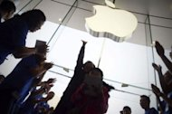 Staff welcome customers at the new Apple store in Beijing's Wangfujing district on October 20. Apple on Saturday opened its biggest Asian store yet in Beijing, with hordes of shoppers descending on the three-floor complex that highlights the growing importance of China to the US tech giant