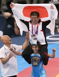 Japan's Saori Yoshida (C) celebrates with her coaches after defeating Canada's Tonya Lynn Verbeek in their women's 55kg freestyle gold medal match during the wrestling event of the London 2012 Olympic Games