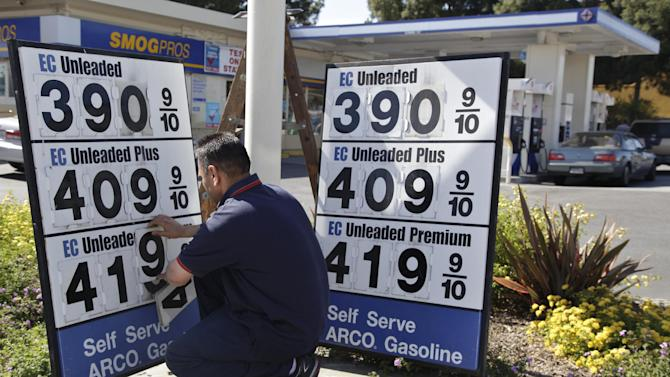 FILE- In this Friday, June 15, 2012, file photo, an Arco gas station worker lowers the prices on a sign at a Arco gas station in Palo Alto, Calif. U.S. crude oil price on Thursday, June 21, 2012, plunged and ended below 79 dollars a barrel for the first time since October 2011 amid global economic concerns. (AP Photo/Paul Sakuma, File)