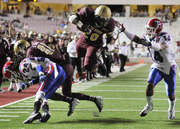 Texas State's Terrence Franks, center, evades Louisiana Tech's Craig Johnson, right, and leaps for a touchdown as Tech's Dave Clark, left, is blocked by Texas' Brandon Smith during the
