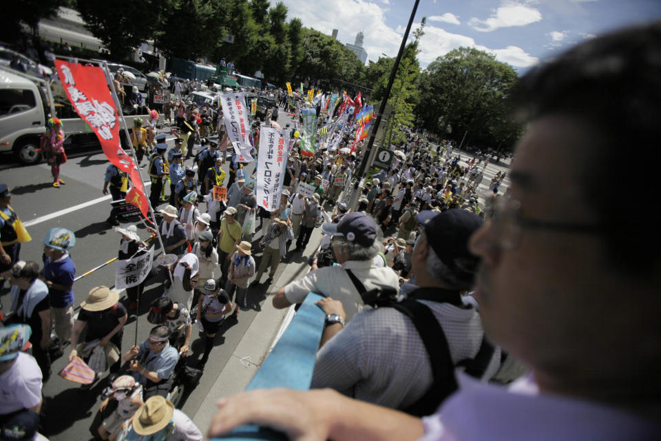 "Anti-nuclear energy protesters march through downtown Tokyo Monday, July 16, 2012. Tens of thousands of people gathered at a Tokyo park, demanding ""Sayonara,"" or goodbye, to nuclear power as Japan prepares to restart yet another reactor, and expressed outrage over a report that blamed culture on the Fukushima disaster. (AP Photo/Greg Baker)"