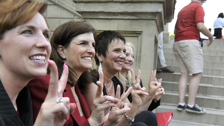 """FILE - This June 18, 2012 file photo shows, from left, Rep. Barb Byrum, D-Onondaga, Rep. Lisa Brown, D-West Bloomfield, playwright Eve Ensler and Sen. Rebecca Warren, D-Ann Arbor, posing for a group picture during an event including a performance of """"The Vagina Monologues"""" by Brown and 10 other lawmakers on the Michigan Statehouse steps, in Lansing, Mich. Brown, who says she was barred from speaking in the Michigan House because Republicans objected to her saying """"vagina"""" during debate over anti-abortion legislation, performed """"The Vagina Monologues"""" with a hand from the author Eve Ensler. (AP Photo/Detroit News, Dale G. Young)"""